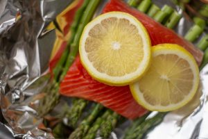 Top down view of the asparagus, salmon, butter and lemon inside a sheet of foil and ready to be wrapped and cooked