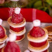 Sifter with powdered sugar dusting the Santa Pancake on a sheet pan