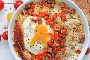Top down view of white bowl loaded with oatmeal, beans, peppers, onions, cheese, bacon and an egg. A hearty meal