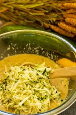 Adding grated zucchini to the wet ingredients in a glass bowl