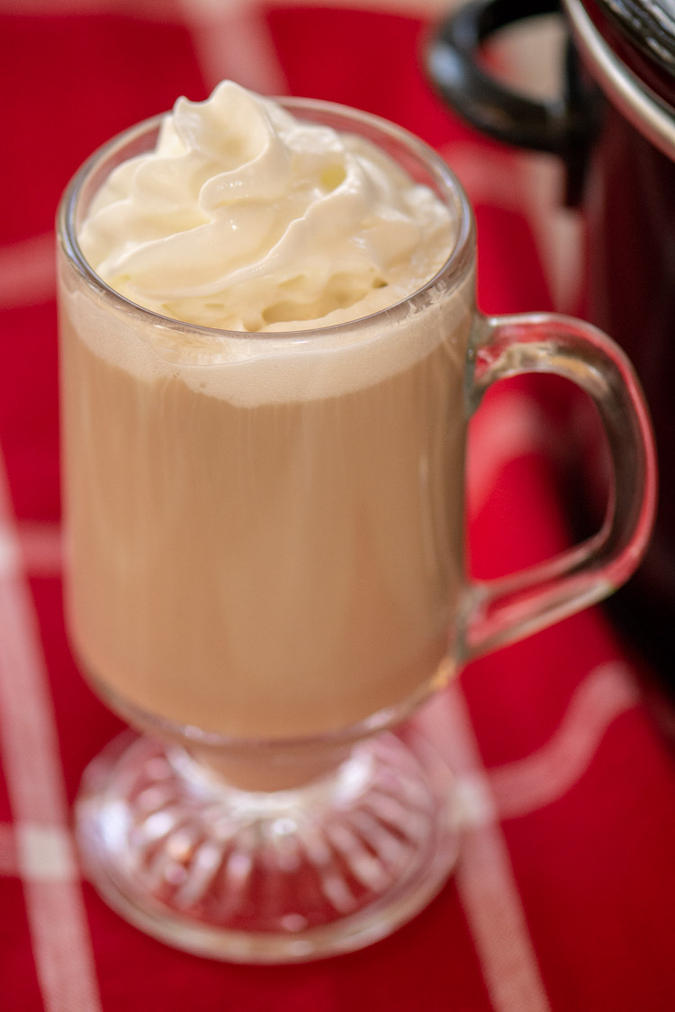 Close up of the holiday coffee in a glass mug with shipped cream on top.
