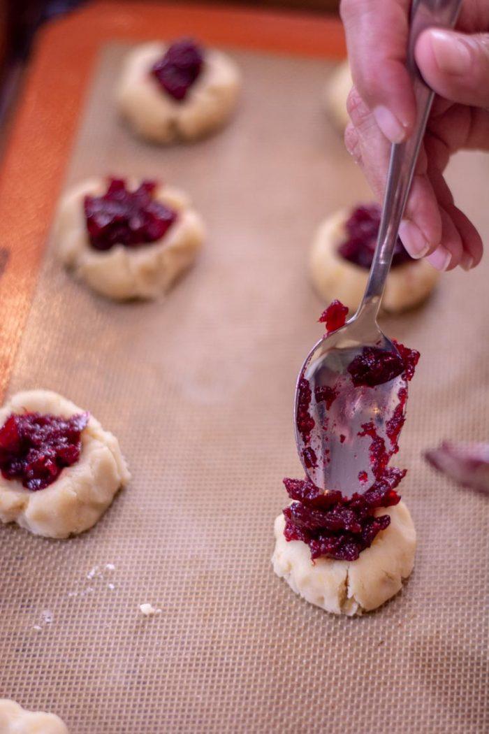 Closeup of the cookie with jam and a spoon to fill the thumbprint