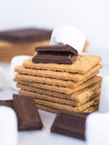 stack of crackers, piles of chocolate chunks and marshmallows to form the Microwave S'More ingredients