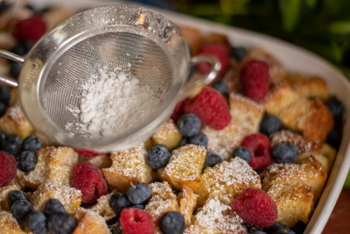 Pan with fresh raspberries and blueberries and sifted powdered sugar