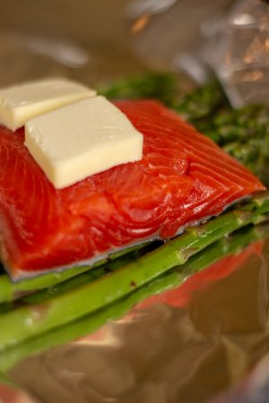 Two pads of butter on the bright pink wild caught coho salmon on an aluminum foil wrap