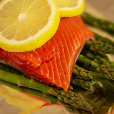 Two lemon slices atop the coho salmon fillet and ready to be wrapped in aluminum foil