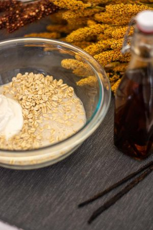 Bowl with the ingredients for Vanilla Overnight Oats and a jar of homemade extract