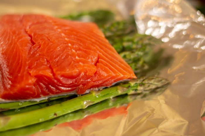Bright Pink Coho Salmon Fillet on a bed of Fresh Green Asparagus in a foil wrap
