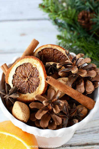 Cup of dried potpourri with oranges and star of anise and cinnamon sticks
