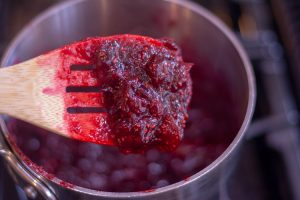 Cranberry Filling is easy to make and will thicken nicely. A wooden spoon is scooping the cranberry sauce out of the pan
