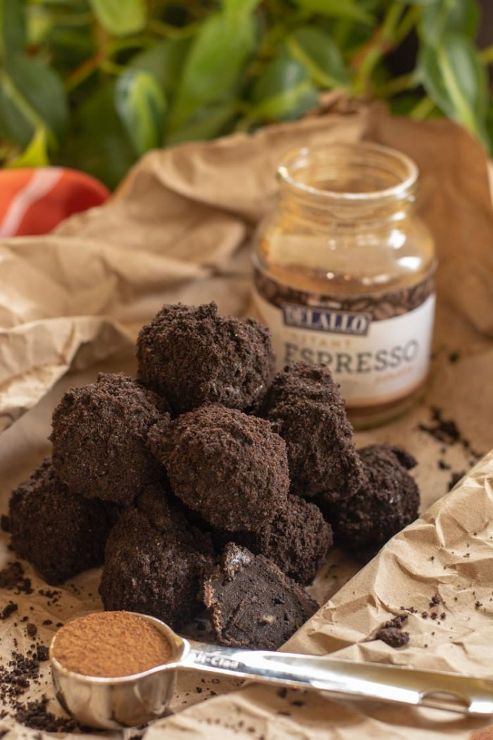Pile of truffles in front of the espresso powder jar and with a tablespoon of espresso in the foreground