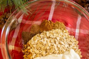 Glass bowl on a red napkin filled with oats, yogurt and all the spices