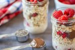 a tablespoon of chia seeds and nutella in front of two jars of overnight oats