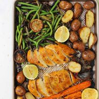 Sliced chicken and veggies on the sheet pan after roasting in the oven.