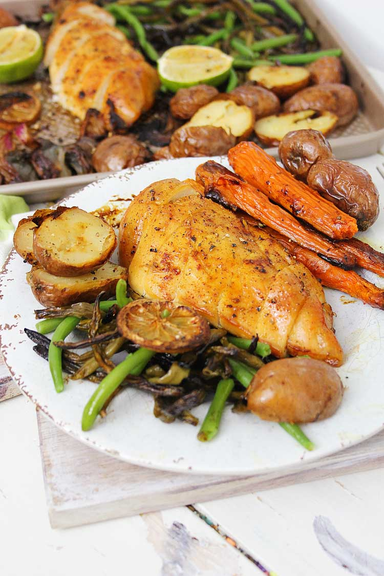 Leftover green beans and carrots are added to the sheet pan. Closeup of the chicken with vegetables