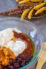 greek yogurt, pumpkin puree, honey, craisins in a glass bowl ready to be added to the mixer