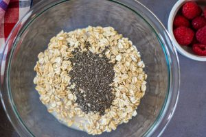 Glass bowl with oats, milk and chia seeds to serve as the beginnings of this recipe
