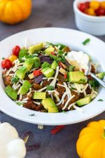 Bowl of pumpkin chili topped with sour cream, sprinkled with a white cheese and chopped avocado