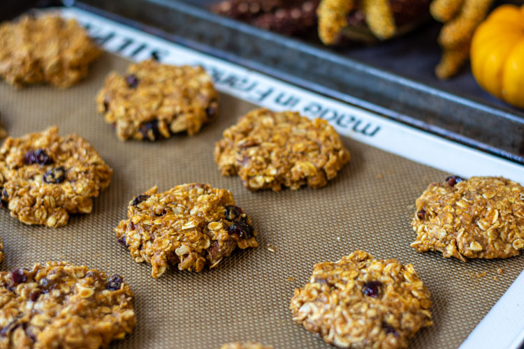 Breakfast cookies on a sheet pan with autumn decor in the background