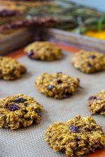 Baked Pumpkin Breakfast Cookies cooling on the Silpat and loaded with Craisins and Oats