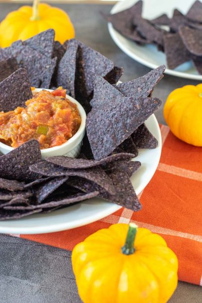 Thick Pumpkin Salsa in a white ramekin with Blue corn chips on a plate