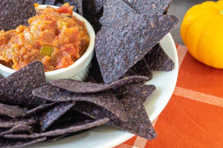 Thick Pumpkin Salsa in a white ramekin with Blue corn chips on a plate