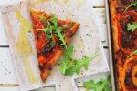 Fresh green arugula adds a crisp tasty to the meatless sheet pan pizza. This slice is on a cutting board and ready to serve