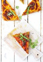 top down view of sliced pizza with arugula on a cutting board with olive oil and ready for dinner