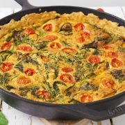 Cast Iron Skillet filled with cooked tomato spinach quiche on a serving trivet