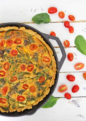 Cast Iron skillet with the fully cooked quiche top as a golden brown