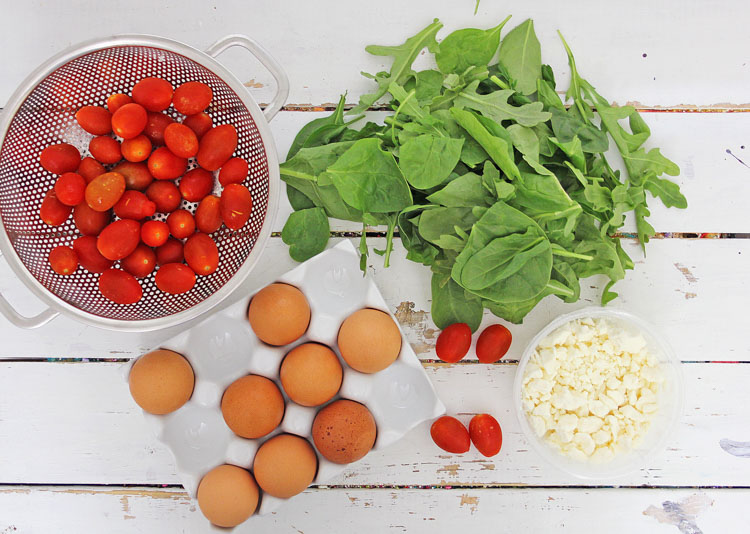 Healthy ingredients of tomatoes, cheese, spinach and eggs on a white table