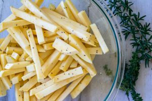 Glass bowl of freshly cut rutabaga fries with a bit of oil and seasoning