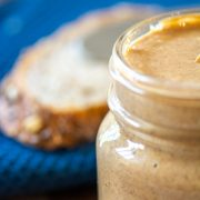 jar of almond nut butter with a blue cloth and slice of bread in the background