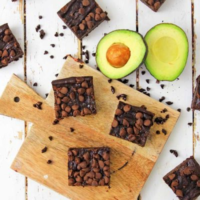 Sliced brownies on a cutting board with a sliced avocado. Loose chocolate chips on the table as well
