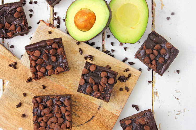 six brownies sliced and spread on the table and cutting board with an avocado cut in half