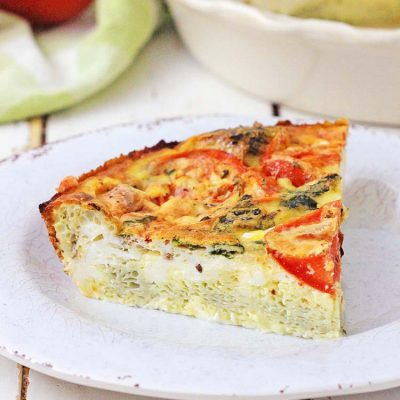 Front view of a fluffy slice of crustless quiche on a plate with the serving dish and a tomato in the background