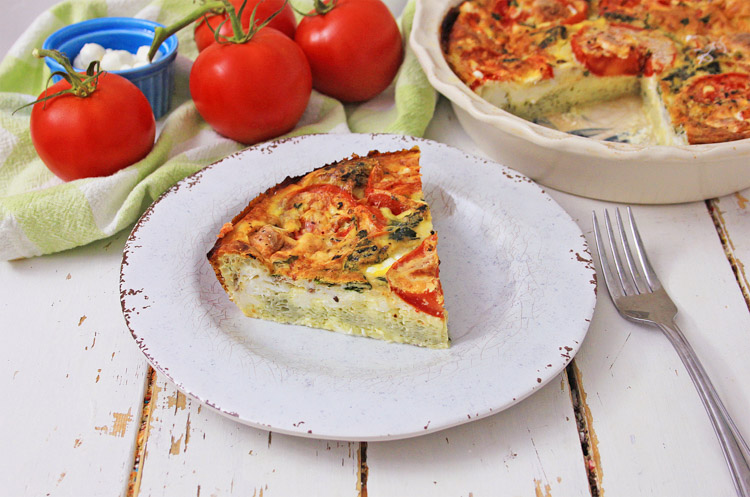 slice of quiche on a plate with tomatoes in the background.