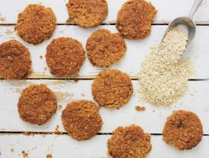 top down view of a bakers dozen oatmeal cookies with a small scoop of oatmeal spilling out to one side