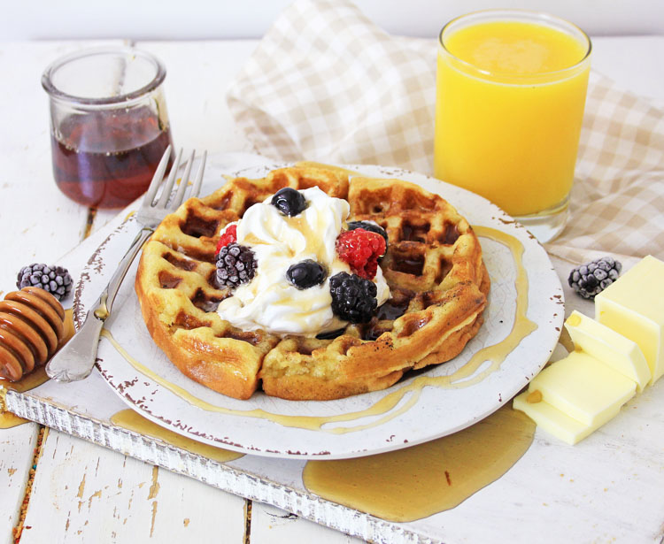 waffle on a plate with orange juice and syrup