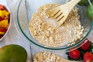 oats and almond milk mixed together in a glass mixing bowl