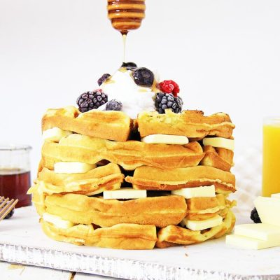 Stack of coconut flour gluten free waffles with pads of butter and topped with frozen berries and honey dripping on top