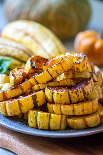 A full plate of roast delicata squash with other fall veggies in the background