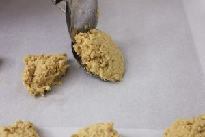 Using spoons to scoop the oatmeal cookie dough on to the parchment lined sheet pan