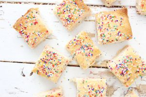 top down view of shortbread cookies with colorful candy sprinkles on a white board