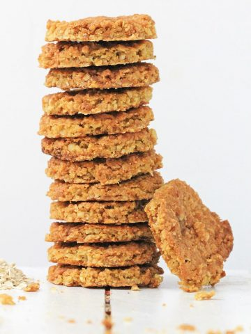 Tall stack of gluten free oatmeal cookies a white board with a white background