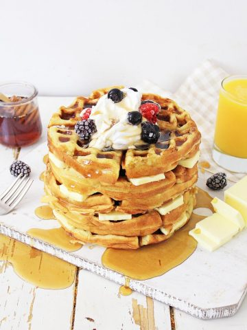 Delicious stack of waffles with syrup spilling over on to the table
