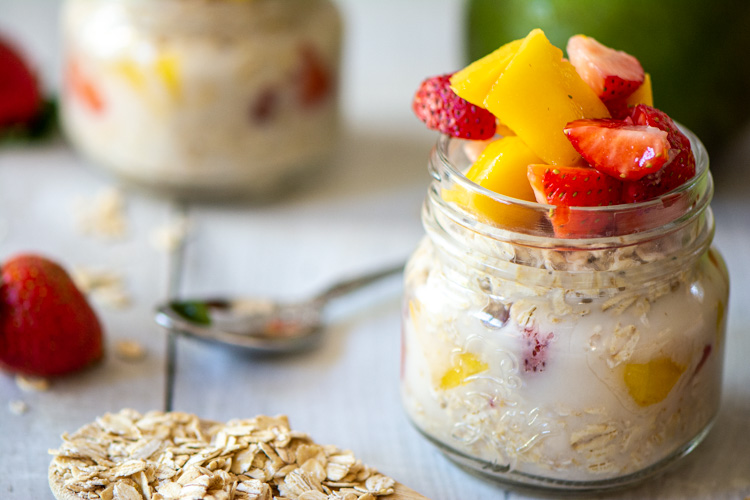 strawberry mango overnight oats in a glass jar with oats and a spoon on a table