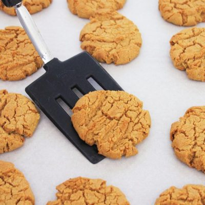 black spatula lifting a sun butter cookie off of the parchment lined sheet pan