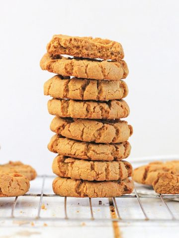 Tall stack of sunflower seed cookies on a wire cooling rack.