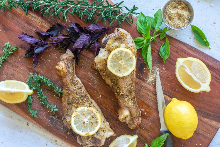 Fully Cooked Turkey Drumsticks on a cutting board with fresh herb, lemons and more seasoning